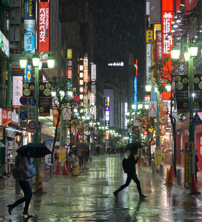 Why is Japan on every traveler's bucket list - Buy My Morning - Tokyo in the heavy rain with two people walking across the wet streets