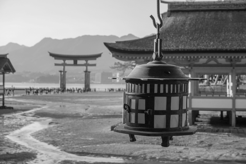 Why is Japan on every traveler's bucket list - Buy My Morning - A black n white view focusing on an old Japanese lamp looking into the distance to Itsukushima Shrine
