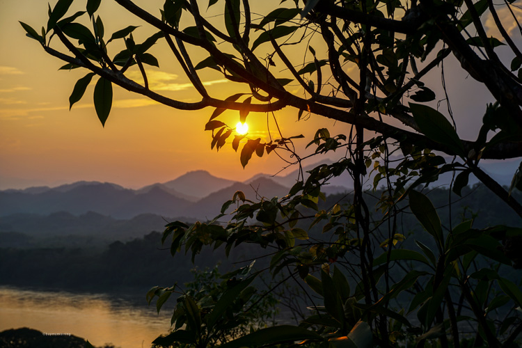 Beautiful sunset view from Mount Phousi, in Luang Prabang Laos. Looking out towards the mountains with a strong orange / red glow across the evening sky | Buy My Morning