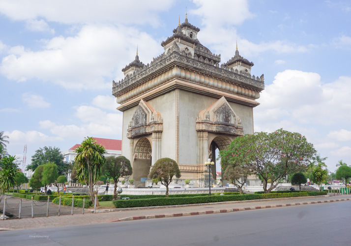 A view of the Patuxai Arch from across the road with the extraordinary angle seeing the complex shapes and small tower designs | Buy My Morning