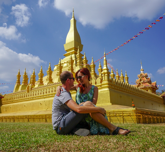 Dan & Fani sitting on the grass close to the Pha That Luang Golden Temple | Buy My Morning