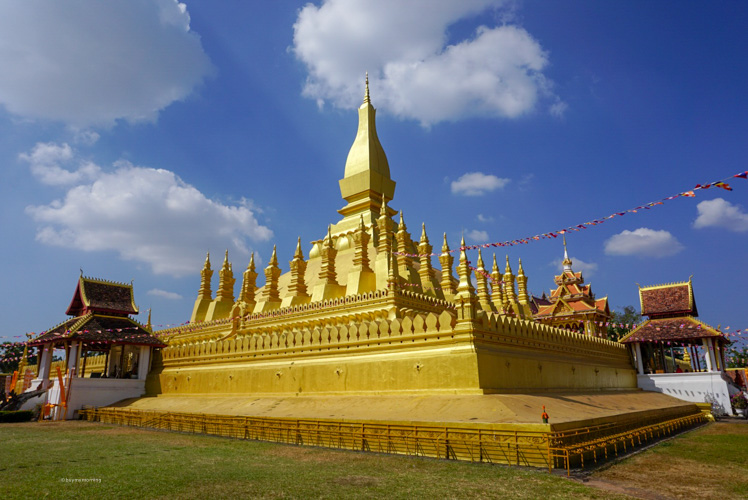 The beautiful Pha That Luang Golden temple in Vientiane Laos with a great blue sky with the sun breaking through | Buy My Morning