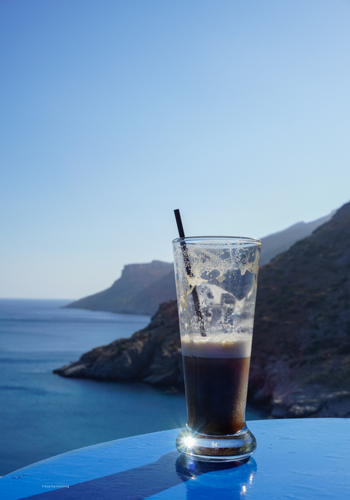 A freddo cappuccino on a beautiful island with a stunning coastline and clear waters in view | Buy My Morning