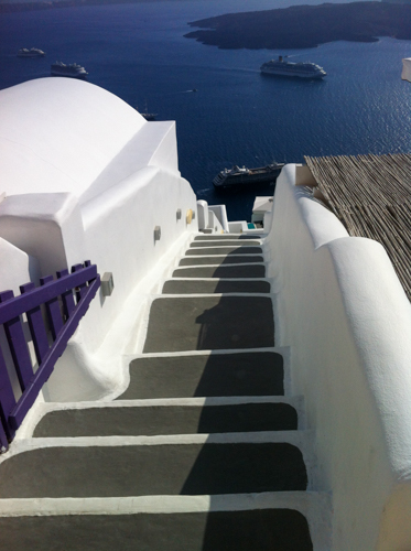 Santorini and the heaven staircase. Irregular grey steps with brilliant white walls and edging taking you to the blue sea | Buy My Morning