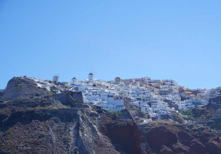 We see you Oia as we cruise by from the sea. the mixture of white building and stunning windmills on display along the cliffs edge | Buy My Morning