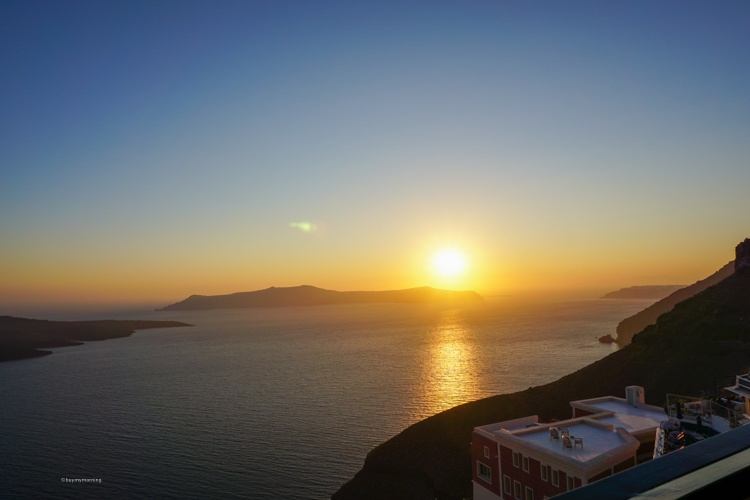 A sunset in Thera with a building top view and the sun escaping into the sea | Buy My Morning