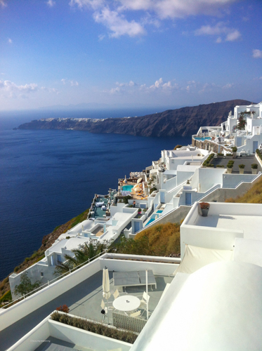 A beautiful clear day on the west side of Santorini with the beautiful white buildings and rocky cliff edge | Buy My Morning