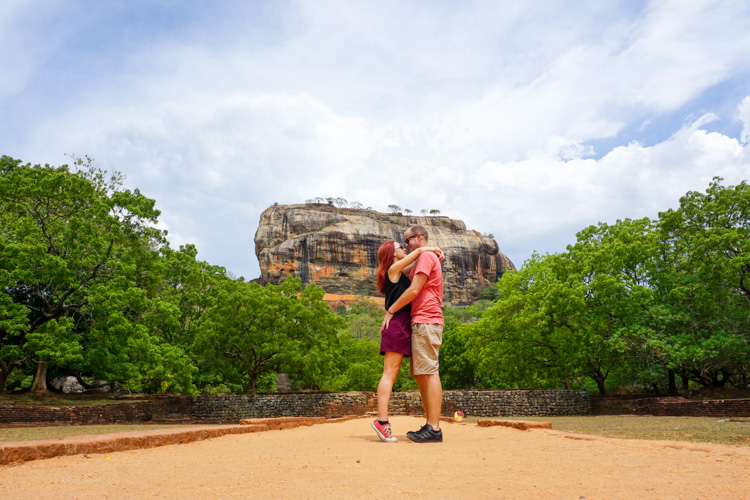 Dan & Fani posing for a photo together in Sigiriya Sri Lanka, with the enormous Lion's Rock in the background | Buy My Morning | Sri Lanka 8 day adventure itinerary